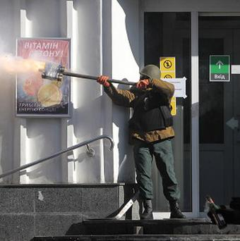 An anti-government protester fires an improvised weapon during clashes with riot police in Kiev (AP)