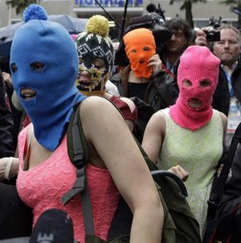 Pussy Riot members Nadezhda Tolokonnikova, in the blue balaclava, and Maria Alekhina, in the pink balaclava, make their way through a crowd after they were released from a police station in Adler, Russia (AP)