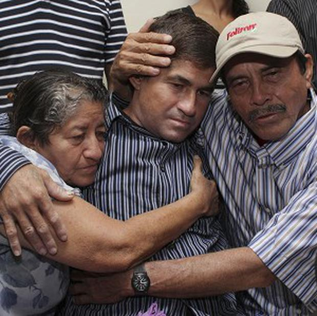 Jose Salvador Alvarenga is embraced by his parents, Ricardo Orellana, right, and Maria Julia Alvarenga in San Salvador (AP)