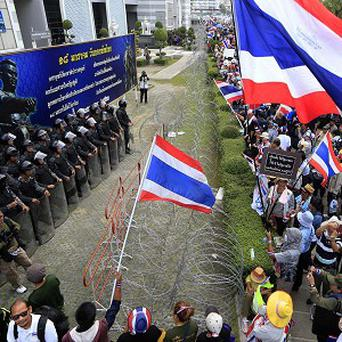 Thai anti-government protesters confront a line of soldiers outside a temporary office of prime minister Yingluck Shinawatra on the outskirts of Bangkok (AP)