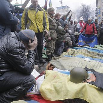 Activists pay respects to protesters killed in clashes with police in Kiev's Independence Square (AP)
