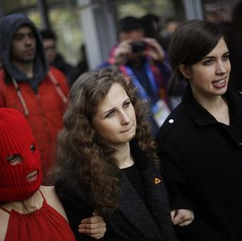 Members of Pussy Riot Nadezhda Tolokonnikova, right, and Maria Alekhina, centre, leave a press conference in Sochi (AP)