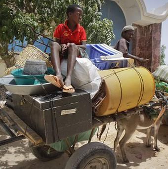 Somali men and boys sit on their belongings on a donkey cart as they flee from Mogadishu after more clashes between militants and pro-government troops (AP)