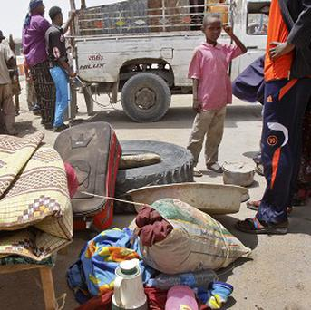 A Somali child stands by his belongings - hundreds of families are fleeing Mogadishu because of increasing clashes between militants and pro-government troops (AP)