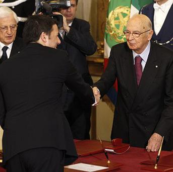 Italian president Giorgio Napolitano (right) shakes hands with premier Matteo Renzi after he took the oath during the swearing-in ceremony (AP)