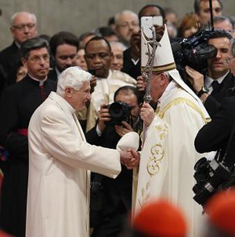 Pope Francis (right) salutes Pope Emeritus Benedict XVI at the end of a consistory inside St Peter's Basilica at the Vatican (AP)
