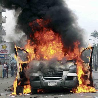 A vehicle being used by an Egyptian television news channel burns after being set on fire by protesters following a protest by supporters of the Muslim Brotherhood in Cairo (AP)