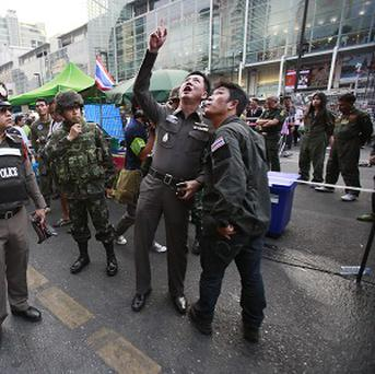 Police officers point to possible evidence at the scene of an explosion at a main protest site in Bangkok (AP)