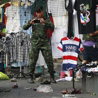 A soldier photographs the scene of an explosion at a protest site in Bangkok (AP)