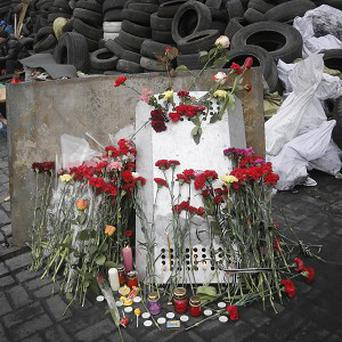 An activist holds flowers and a chocolate as he guards one of the barricades heading to Kiev's Independence Square (AP)