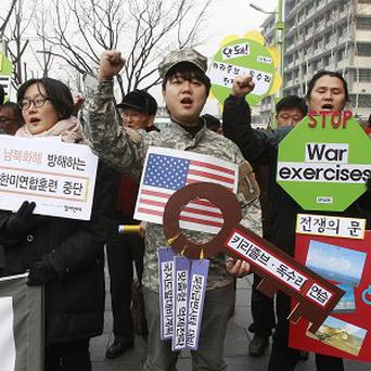Protesters shout slogans denouncing the annual joint military exercises between South Korea and the US, during a rally near in Seoul (AP)
