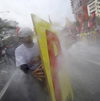Water cannons are sprayed at protesters as they force their way closer to the US embassy in Manila (AP Photo/Bullit Marquez)