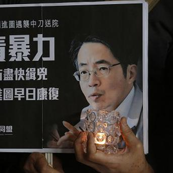 A protester holds a placard with a picture of former Ming Pao chief editor Kevin Lau (AP)