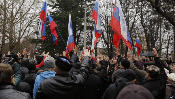 Pro-Russian demonstrators wave Russian and Crimea flags and shout slogans during a protest in front of a local government building in Simferopol, Crimea (AP)