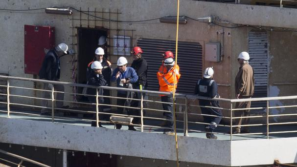 Captain Francesco Schettino, fourth from left, talks on the upper deck of the wreck of the Costa Concordia (AP)