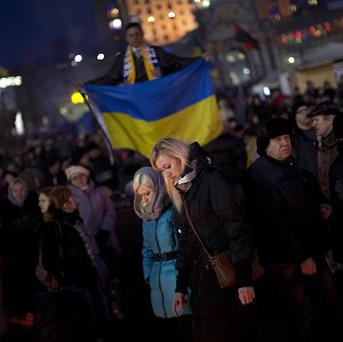 People gather at a memorial to those killed in clashes with police in Kiev's Independence Square (AP)