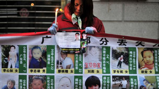 A woman holds a candle behind photos of missing children after Chinese police rescued 382 abducted babies and arrested 1,094 suspects in a national operation into baby trafficking (AP)