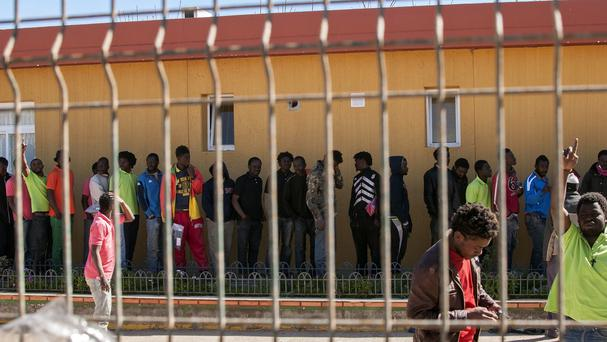 Migrants queue up inside a holding centre after climbing a fence to enter the Spanish enclave of Melilla (AP)