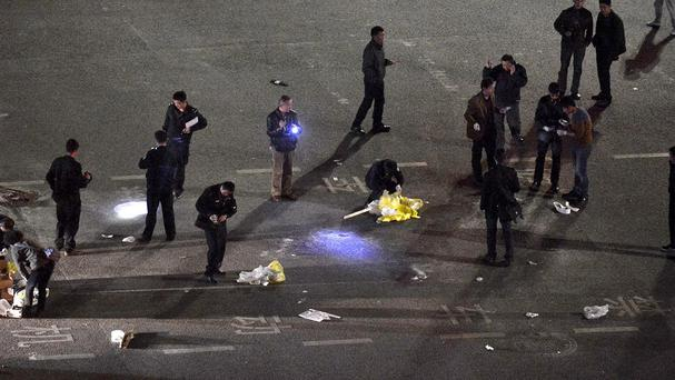 Police officers investigate the crime scene outside a railway station after an attack by knife wielding men leaving some 27 people dead in Kunming, in south western China (AP)