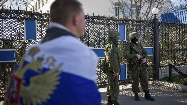A man wearing the Russian national flag walks past an entrance to the general staff headquarters of the Ukrainian Navy in Sevastopol (AP)