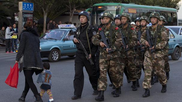 Armed police patrol a street near Kunming station, where assailants slashed scores of people with knives on Saturday