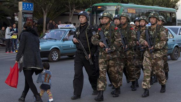Armed police patrol a street near Kunming station, where assailants slashed scores of people with knives