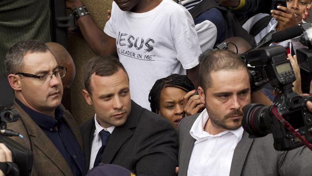 Oscar Pistorius, centre, is escorted out by police officers as he leaves the high court on the second day of his trial in Pretoria, South Africa (AP)