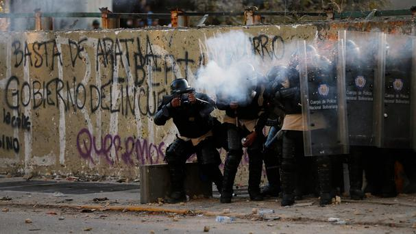 Police officers fire tear gas at demonstrators during clashes in Caracas (AP)
