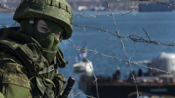 A Russian soldier guard a pier where two Ukrainian naval ships are moored, in Sevastopol (AP)