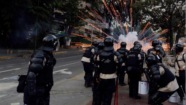 Police take cover from exploding fireworks launched at them by anti-government demonstrators during clashes in Caracas, Venezuela (AP)