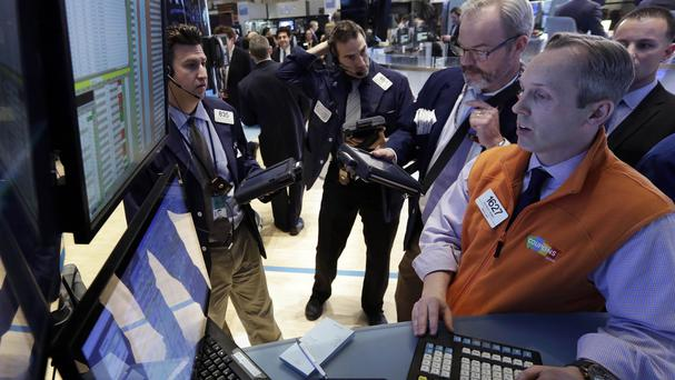 Traders gather at the post of specialist Patrick Kenny, right, on the floor of the New York Stock Exchange (AP)