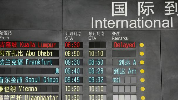 The arrival board at the International Airport in Beijing shows a Malaysian airliner is delayed (AP)