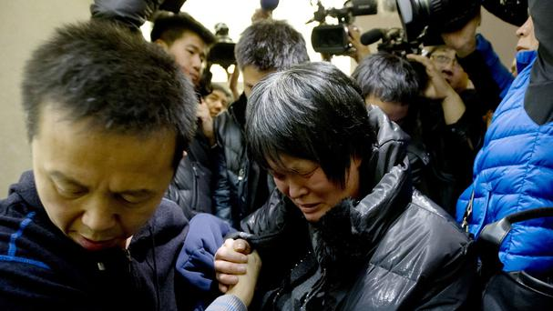 A Chinese relative of passengers aboard a missing Malaysia Airlines plane cries as she leaves a hotel room for relatives or friends of passengers aboard the missing plane (AP)