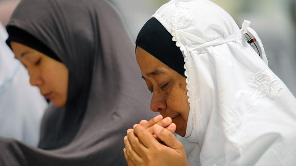 A Malaysian Muslim woman cries as she offers a special prayer for passengers aboard a missing plane, at a mosque in Putrajaya (AP)