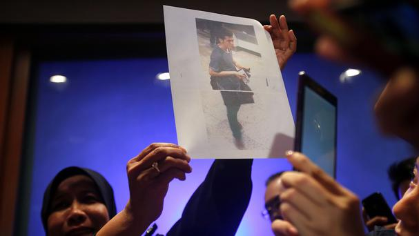 A picture of a 19-year old Iranian, identified by Malaysian police as Pouria Nour Muhammad Mehrdad, who boarded the now missing Malaysia Airlines jet MH370 with a stolen passport, is held up by a Malaysian policewoman (AP)