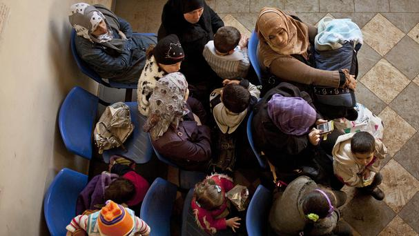 Syrian women wait with their children at the UN refugee agency's registration centre in Zahleh, in Lebanon's Bekaa Valley (AP)