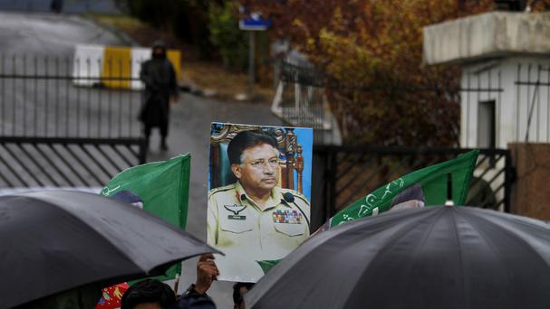 A supporter of former Pakistani president Pervez Musharraf, holds a photo of him, at the main entrance of a court in Islamabad (AP)