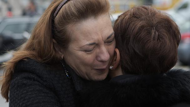 Pilar Manjon, the president of the 11M train victims association, left hugs a woman outside Atocha train station in Madrid (AP)