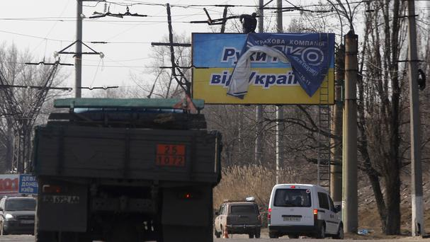 Workers place an advertisement over a poster which reads: 'Hands off Ukraine' in Perevalsk, eastern Ukraine, ahead of the referendum in Crimea (AP)