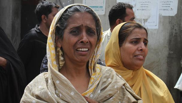Local residents of Karachi's troubled area of Lyari mourn the victims of a gun attack (AP)