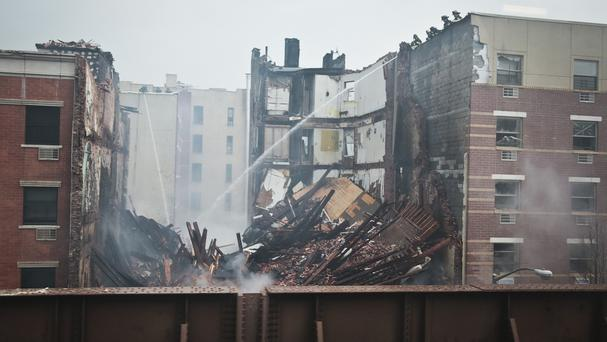 Firefighters spray water on the smouldering debris from an explosion in Harlem (AP)
