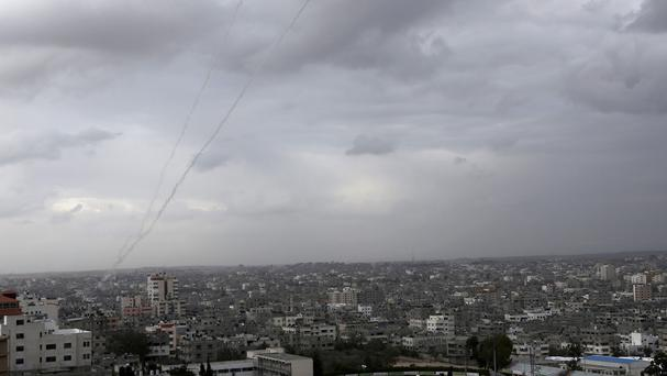 A trail of smoke from rockets fired by Palestinian militants towards Israel is seen in the skies above Gaza City (AP)