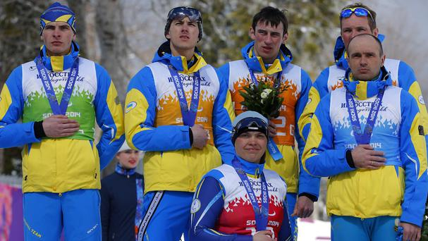 Ukraine's team cover their silver medals with their hands after finishing second in cross country 4x2.5km open relay at the 2014 Winter Paralympics in Sochi, Russia (AP)