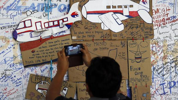 A man takes a picture of the messages board for passengers aboard a missing Malaysia Airlines plane at Kuala Lumpur International Airport (AP)
