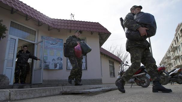 Ukrainian air force officers walk with their bags at the Belbek airbase, outside Sevastopol, Crimea (AP)