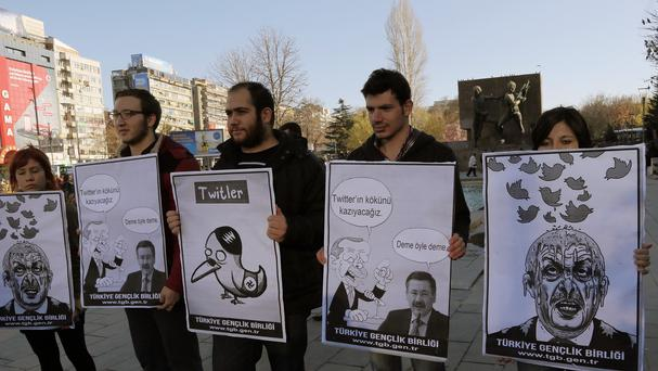 Members of the Turkish Youth Union hold cartoons depicting Turkey's prime minister Recep Tayyip Erdogan during a protest against a ban on Twitter (AP)