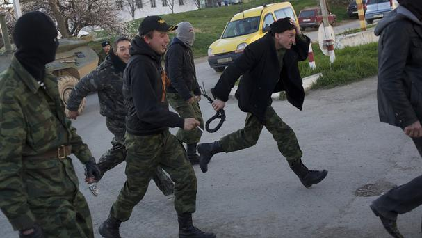 Cossacs and Pro-Russian militia members run toward the Belbek airbase after Russian soldiers took control over it, outside Sevastopol, Crimea (AP)