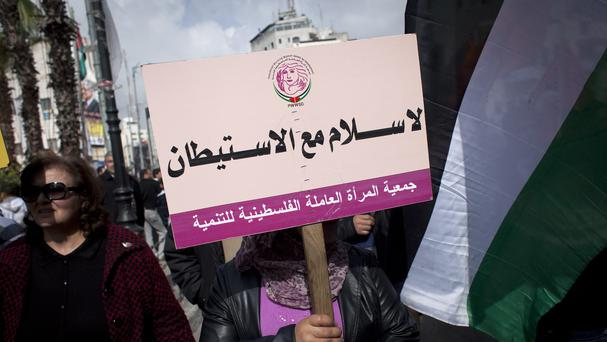 A protester holds a placard during an anti-peace talks rally in the West Bank city of Ramallah (AP)