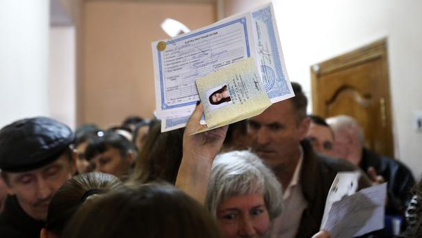 Residents gather in a passport centre to submit papers to apply for Russian passports in Simferopol, Crimea on Friday