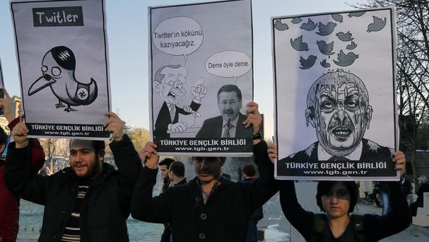 Members of the Turkish Youth Union hold cartoons depicting Turkey's prime minister Recep Tayyip Erdogan during a protest against a ban on Twitter